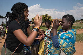 Buffalo State junior Ashanti Bryant plays with a child in the Rwandan village of Gashora during an AFP trip to visit with the leaders of women-led cooperatives and entrepreneurial projects in the town.