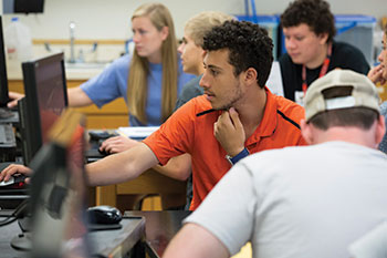 TTU students work on computers during an astronomy class; faculty and students converse in a science lab