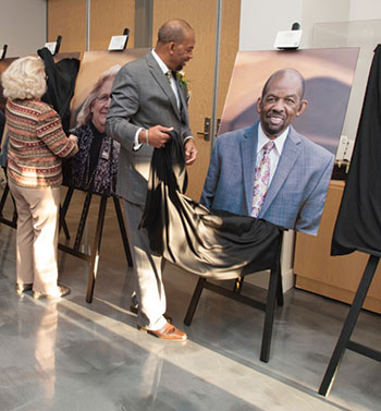 """Jerome Ratchford (right) and Carol Pope (left) unveil their portraits at the """"Emerging from Within"""" reception."""