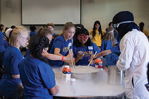 STEM for Girls participants along with a UC Davis STEM student mix liquid nitrogen with heavy whipping cream, sugar, and vanilla to make ice cream. (photo by Srinu)