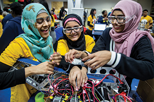 Detroit International Academy students Zannatun Alim, Tayebah Chowdhury, and Tunzzina Chowdhury rush to finish their team's robot at the annual MEZ Open House at the UMich Detroit Center in February 2016. (photo by Joseph Xu/Michigan Engineering, Communications & Marketing)