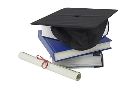 Photo of a graduation cap on top of books next to a diploma