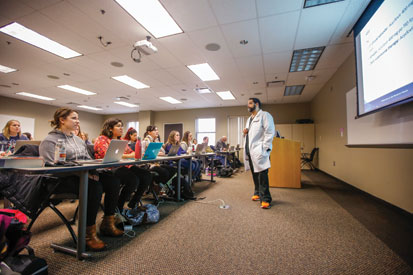 Luis Rosario-McCabe, an assistant professor of clinical nursing at the University of Rochester School of Nursing, speaks to accelerated bachelor's students in a women's health class.