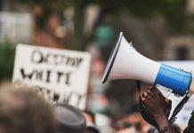 Photo of a Black protestor holding a megaphone.