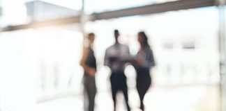 Out of focus photo of three people standing and talking