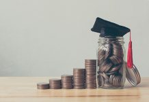 Photo of several stacks of coins lined up next to a jar of coins with a graduation cap placed on the top.