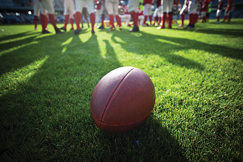 Photo of a football sitting on a field with players standing in the foreground