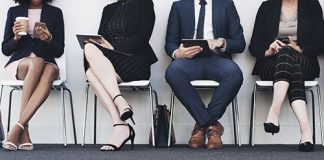 Photo of people dressed in business professional clothing sitting in a line of chairs