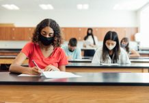 Photo of students wearing face masks while doing work in a classroom.