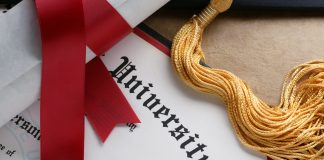 Photo of a university diploma with a golf tassel and rolled diploma with red ribbon