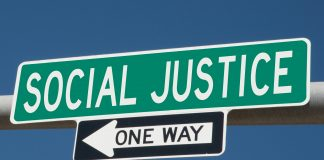 A sign that reads Social Justice above a sign with an arrow that says One Way