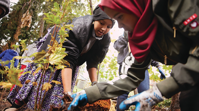 Photo of students wearing gloves and working in a community garden.