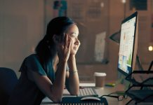 Photo showing a woman sitting at a desk in front of a computer making a concerned face.