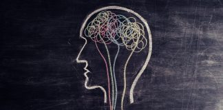 Photo of a hand using chalk to draw a head with spirals inside the brain