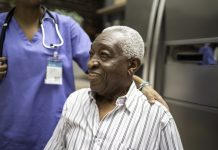 Photo of an older Black man receiving healthcare services from a Black nurse.