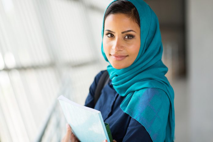 Islamic college student holds a book while looking into camera