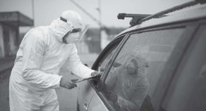 Photo of a man wearing personal protective equipment while standing next to a vehicle with the window rolled down.