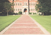 Photo of a brick pathway leading to a building on a college campus.