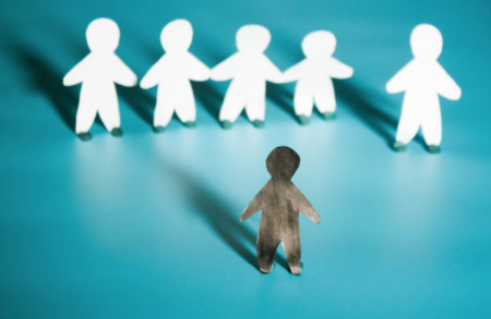 Illustration showing a black cutout of a person standing before a row of six white cutouts.
