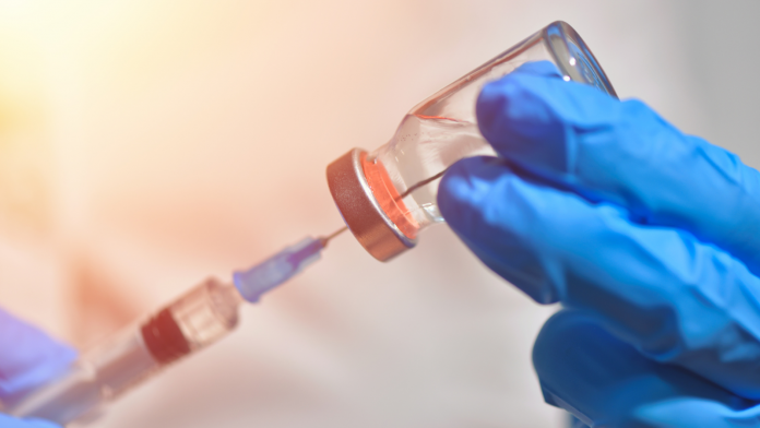 Photo of a medical professional using a syringe to administer a vaccine.