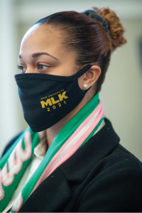 Photo of a woman wearing a mask that says MLK 2021.