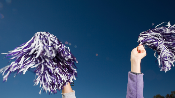 Photo of a cheerleader's hands holding pom poms.