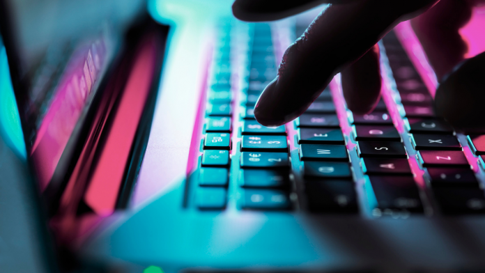 Photo of a hand typing on a laptop keyboard.