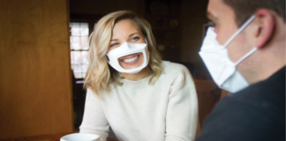 Photo of a woman wearing a transparent face mask while talking to a man wearing a facial mask.