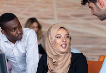 Photo of a woman wearing a hijab in front of a computer speaking with two men.
