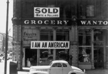 """Black and white photo of a storefront with a sign that reads """"I am an American"""""""