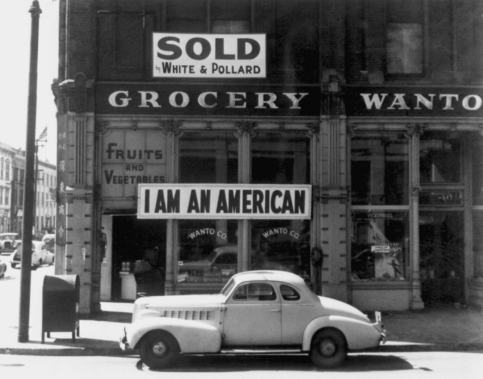 Black and white photo of a storefront with a sign that reads
