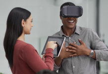 Photo of a man wearing a virtual reality headset while a woman holds an iPad next to him.