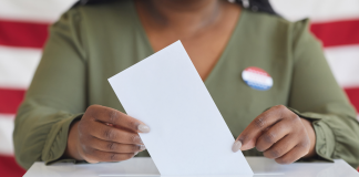 Photo of a Black woman pictured from neck down casting her vote in a ballot box while posed in front of American flag.