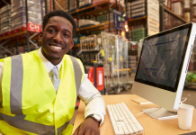 Photo of a Black man in a safety vest seated in front of a computer in a warehouse