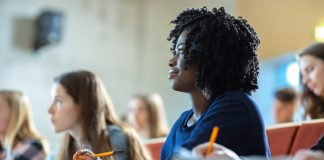 Photo of a Black woman student sitting in a lecture hall surrounded by peers.