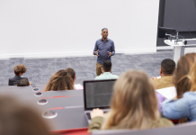 Photo of a Black professor giving a lecture to a room filled with college students
