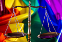 Photo of a scale in front of a LGBTQ pride flag