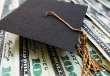 Photo of a graduation cap on a pile of $100 bills