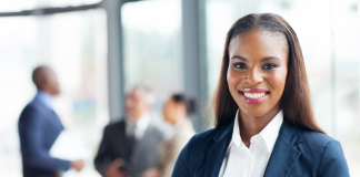 Photo of a Black woman in business attire standing in the foreground with other people in the background