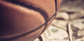 Photo of a basketball sitting on top of money.