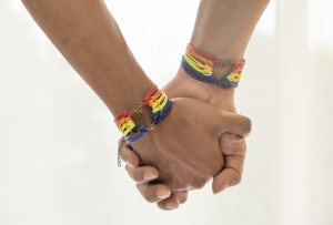 Photo of two people holdings hands and wearing LGBTQ Pride bracelets.