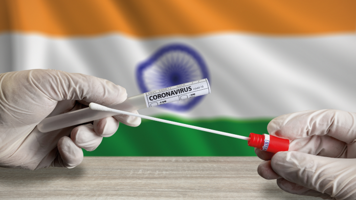 Photo of gloved hands holding a COVID-19 test in front of an Indian flag.