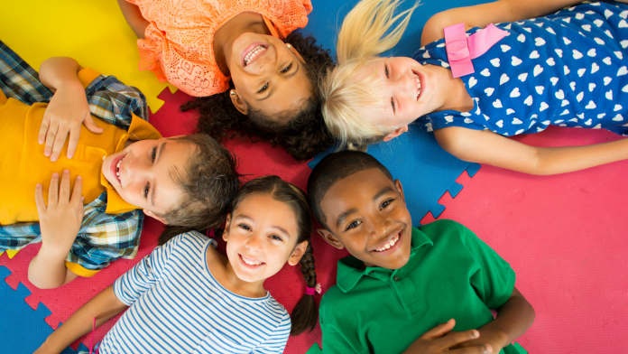 Photo of five diverse children lying on a puzzle mat.