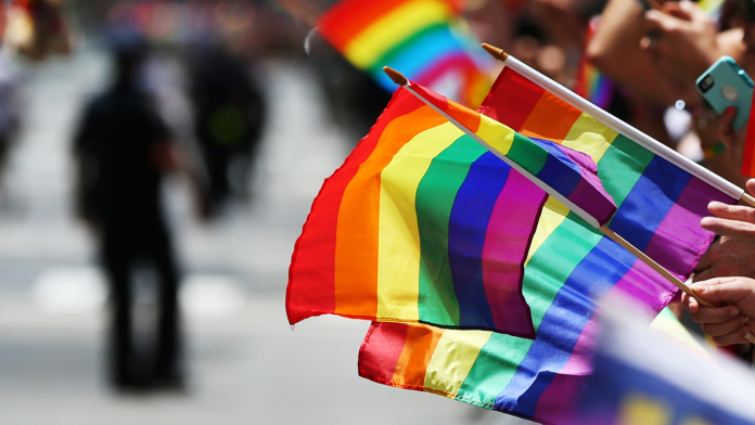 Photo of people holding LGBTQ Pride flags during a Pride Month march.