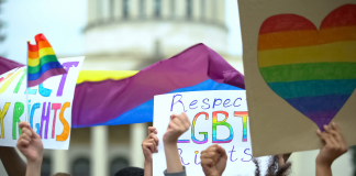 Photo of a group of protestors holding signs demanding LGBTQ rights.