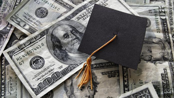 Photo of a graduation cap on a pile of U.S. 100 dollar bills